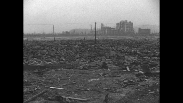 View of ruins through denuded trees in Hiroshima a city devastated after World War II atomic bombing / man walks through extensive rubble / twisted...