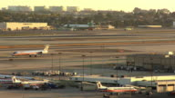 WS View of runway at Los Angeles International Airport with American Airlines passenger jet in foreground taxiing on one runway to terminal while United Airlines jet in background is taking off from other runway / Los Angeles, California, USA