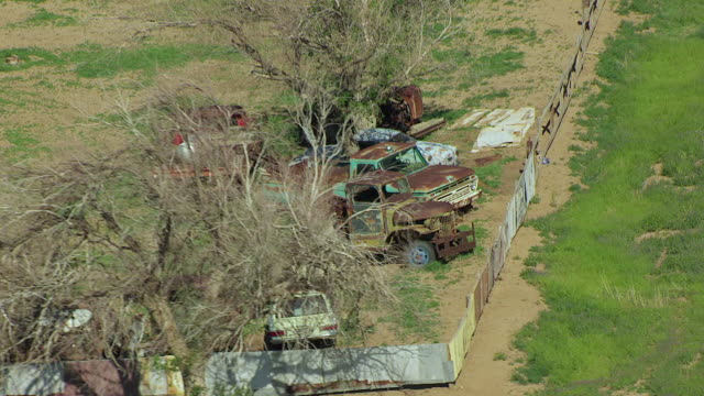 WS AERIAL ZO View of Rusty old cars at farmland / Boise City, Oklahoma, United States