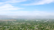 WS ZO AERIAL POV View of San Fernando Valley with cityscape, mountain range in background / Los Angeles County, California, United States