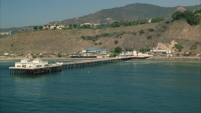 WS POV View of sea and beach with traffic on coastal road / California, USA