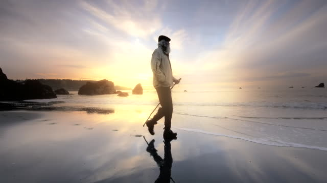 WS SLO MO TS View of Senior Man walking on Beach at sunset time / Port Orford, Oregon, United States