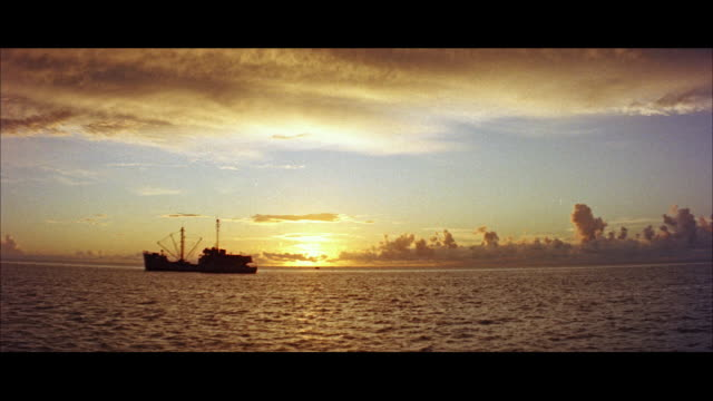 MS View of ship in ocean at sunset