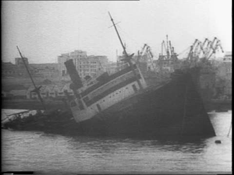 View of ship through lifesaver and portal hole / bow of ship cutting through waves / American flag / shots of guns firing from battleship / Vichy...