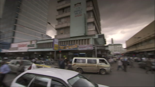 WS PAN View of shopping district, pedestrians, cars on street / Nairobi, Nairobi Province, Kenya