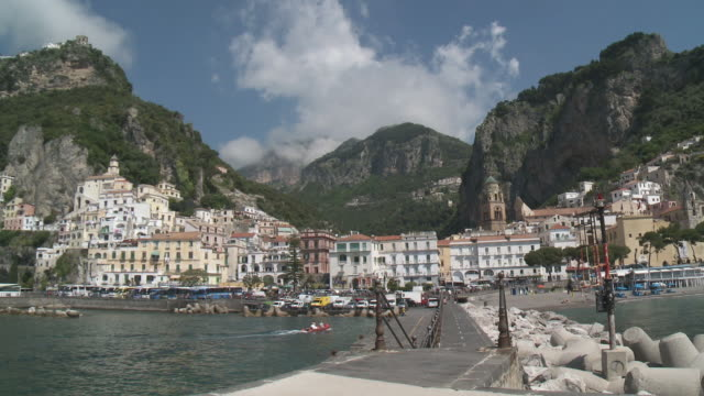 WS View of small city on mountain and Boat moving towards Amalfi marina / Amalfi, Campania, Italy