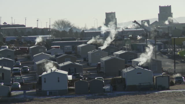 View of smoke coming out of trailers and cars at trailer park outside of Williston, North Dakota.
