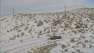 WS POV View of snowplow driving on snow covered road with rocky mountain landscape / Mammoth Lakes, California, USA