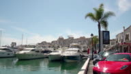 MS View of Some motor boats attached on jetty with cars standing at Puerto Banus near Marbella / Puerto Banus, Andalusia, Spain