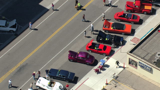 MS DS TU AERIAL View of spectators looking at colorful cars parked on street during Nelsons Old Town Car Show / Fort Collins, Colorado, United States