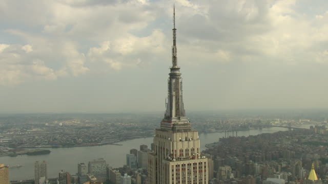 WS AERIAL View of Spire and Observation Deck of Empire state building with river and sky / New York, United States