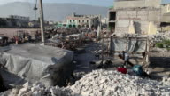 WS View of Street scene with mountains vendor and piles of rubble line street / Port-au-Prince, Haiti