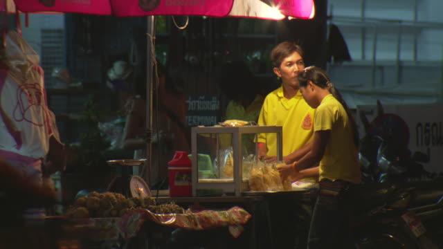 WS View of Street vendors arrange food in their cart on Mae Sai main street at night / Mae Sai, Chiang Rai, Thailand