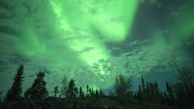 WS T/L View of strong aurora behind rolling clouds / Yellowknife, Northwest Territories, Canada