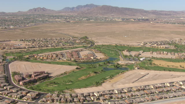 WS AERIAL ZI View of suburban neighborhood under construction and Tuscany Golf Club with green grass and small lakes / Henderson, Nevada, United States