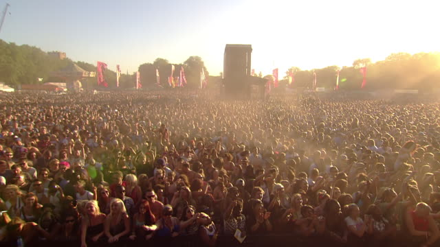 WS POV View of Sun cutting across festival crowd dancing with hands up in air  / Victoria Park, London, United Kingdom