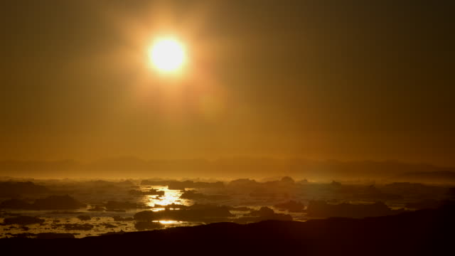 WS T/L View of Sun moving across orange sky as it sets over ocean filled with icebergs / Ilulissat, Greenland