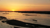 WS View of sun setting down over river  Platte Flocks of Sandhill Cranes Grus canadensis flying / Kearney, Nebraska, United States