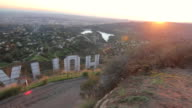 PAN MS View of  sun setting in Hollywood hills from  behind Hollywood sign  / Los Angeles, California