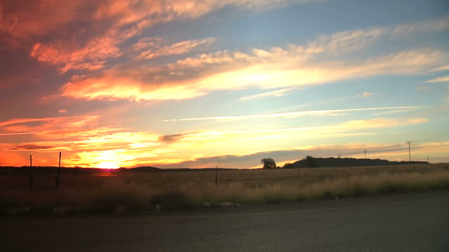 WS View of Sun setting over fields behind clouds / Free State, South Africa
