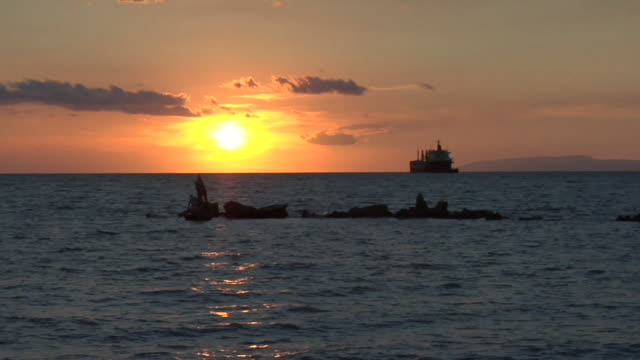 View of sunset at ocean with boat and ship / Haiti