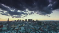 WS T/L View of sunset over shinjuku business and shopping area with dark clouds moving in sky / Tokyo, Japan