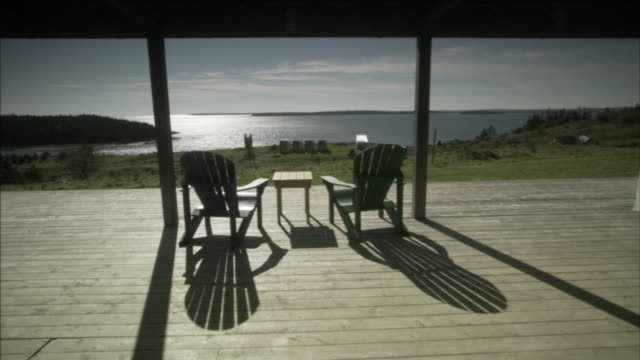 WS View of table and chairs in balcony with sea in background / Upper Kingsburg, Nova Scotia, Canada