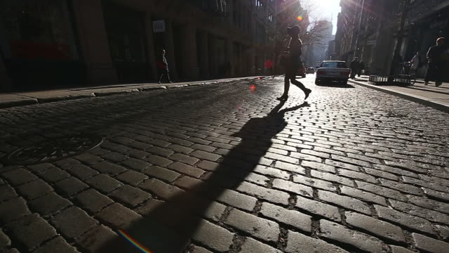 WS TU View of taxi running and pedestrians crossing on shining stone pavement street at Soho / New York, United States