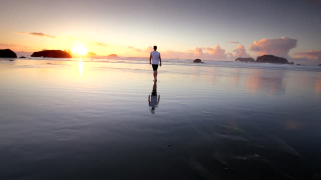 WS SLO MO POV View of teen boy walking on beach at Sun setting / Bandon, Oregon, United States