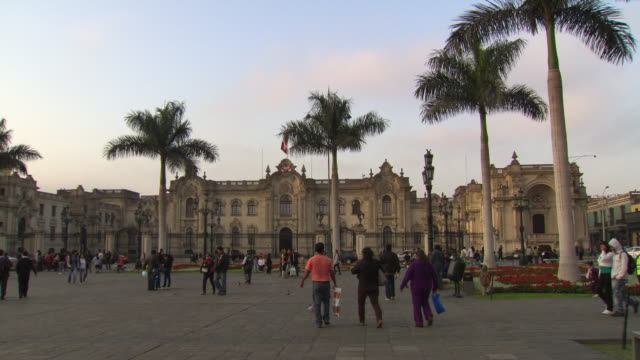 'View of the Government Palace of Peru/House of Pizarro [Casa de Pizarro], from center of Plaza Mayor/Plaza de la Armas of Lima, with lots of tourists milling around, Lima, Peru'