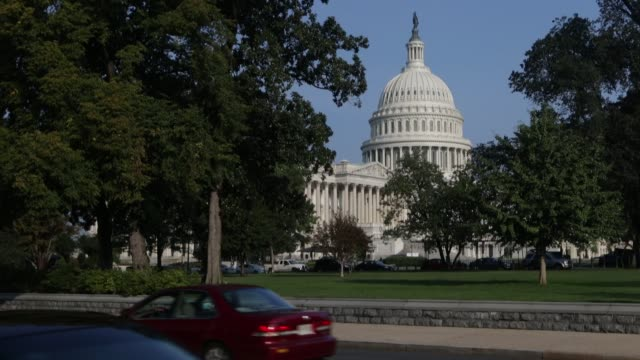 view of the US Capitol building from across the street / vehicles driving past / House of Representatives building in view US Capitol and House of...