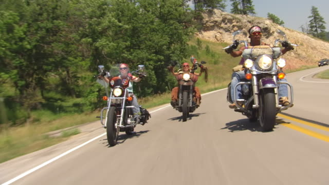 WS POV View of Three women riding their motorcycles on highway during Sturgis Motorcycle Rally / Sturgis, South Dakota, United States