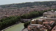 WS AERIAL View of Tiber river through city and passing Castle of Saint Angelo with St Peter Basilica and VATICAN / Rome, Italy