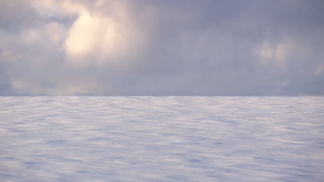 WS AERIAL View of Tight lateral over ice of glacier (speedy clouds) / Iceland