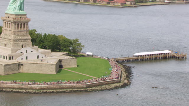 MS AERIAL ZO View of tourists walking on pathway at base of Statue of Liberty on Liberty Island to statue of liberty / New Jersey, United States