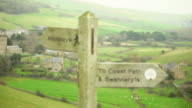 CU RF View of town and sign reading abottsbury & swannery / Abbotsbury, England, United Kingdom