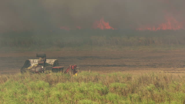 MS AERIAL ZI View of tractor driving and other tractor with fire in background / Lake Okeechobee, Florida, United States
