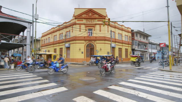 WS PAN View of traffic moving as light turns green few old colonial buildings line street / Iquitos, Maynas, Peru