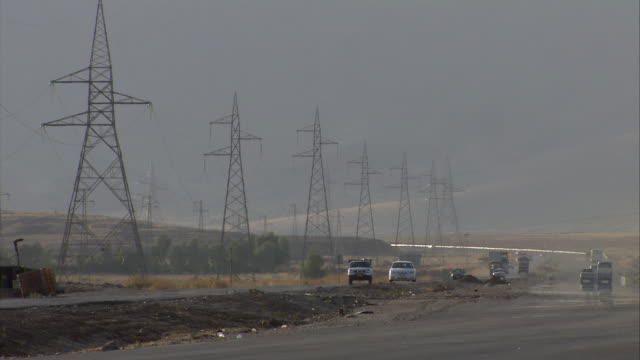 WS View of Traffic moving on highway in front of hills and telephone poles / Sulaymaniyah, Kurdistan, Iraq