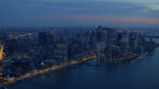 WS AERIAL View of traffic moving on Westside highway and Brooklyn and Manhattan bridges in lower Manhattan near Hudson River at evening / New York, United States