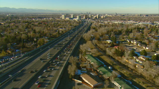 WS POV AERIAL View of traffic on I-25 with the city of Denver and Rocky Mountains in background / Denver, Colorado, USA