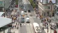 MS View of Traffic, TTC streetcar and pedestrians moving at Yonge and Dundas square / Toronto, Ontario, Canada
