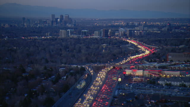 WS POV AERIAL View of traffic with downtown Denver and rock mountains in background / Denver, Colorado, USA