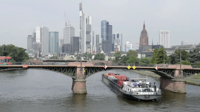 WS View of tram on bridge over river main and cargo ship with skyline and financial district / Frankfurt am Main, Hesse, Germany
