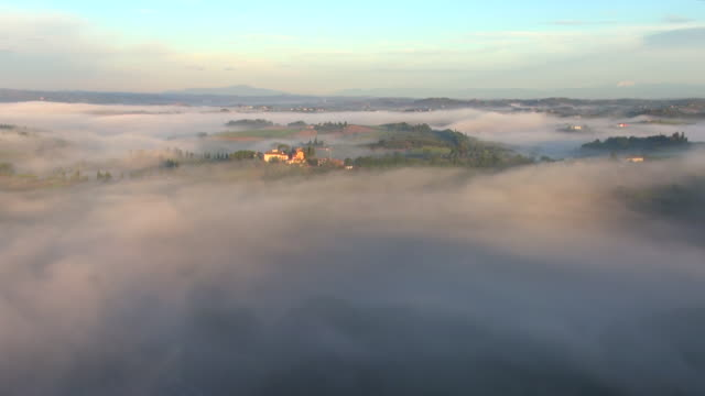 WS AERIAL View of Tuscan hills and villa in early morning fog / San Gimignano, Tuscany, Italy