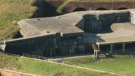 WS AERIAL ZO View of two people walking around Fort Morgan and reveal entire fort / Alabama, United States