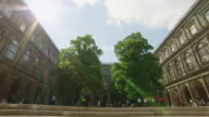 WS LA View of University of Wien with people moving and trees / Vienna, Austria