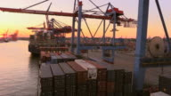 WS View of unloading containers in container ship on container terminal in harbour at sunset / Hamburg, Germany