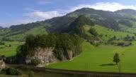 WS AERIAL View of village with rail tracks and landscape / Lake Lauerz, Schwyz, Switzerland