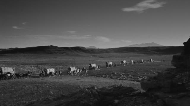 WS View of wagon train traveling through desert